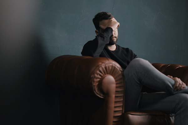 Depressed man sat on a sofa holding his head in his hands