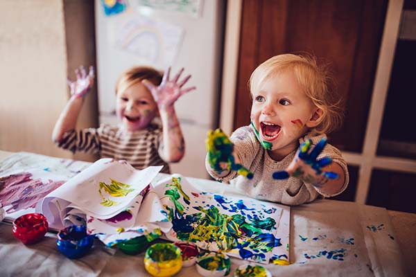 Happy little girls with dirty hands and faces having fun being creative with finger painting at YMCA Hayes Lane Nursery