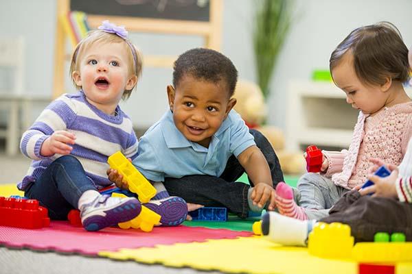 three babies playing on soft mats at YMCA Pelsall Lane Nursery