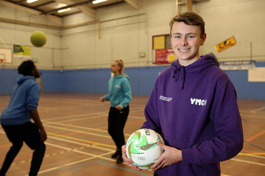 young man holding a football at ymca sports hall