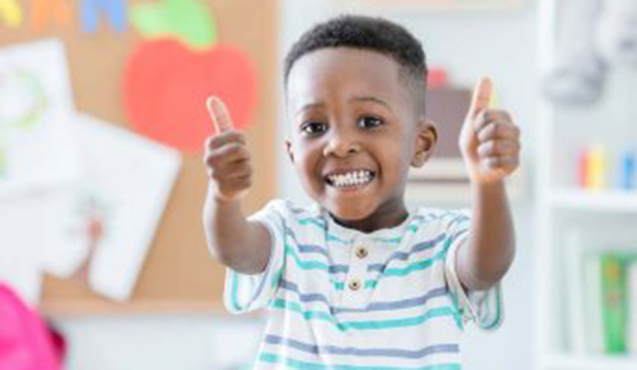 happy young boy with thumbs up at YMCA day care