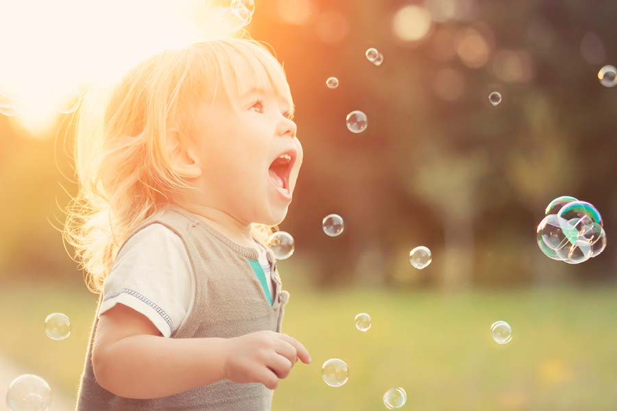 happy boy chasing bubbles in day care garden