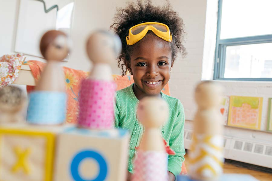 smiling girl at YMCA nursery playing with wooden toys