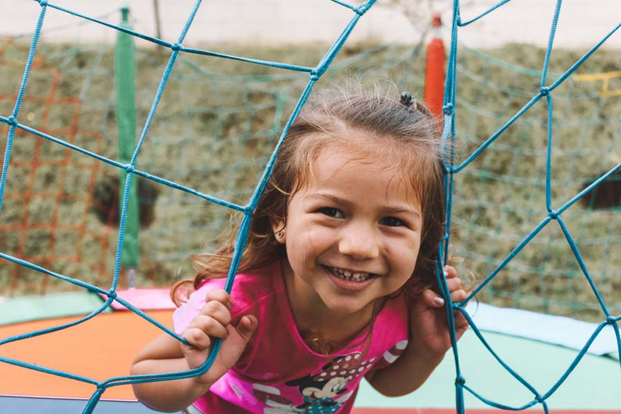 happy smiling girl playing on a climbing frame in YMCA nursery garden